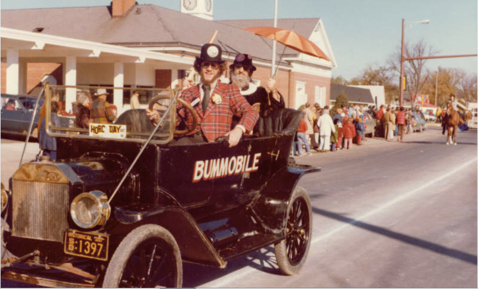 Digital Library of South Dakota (DLSD) Gordon Niva as Weary Wil drives the Bummobile on Fifth Avenue during the 1975 Hobo Day parade.