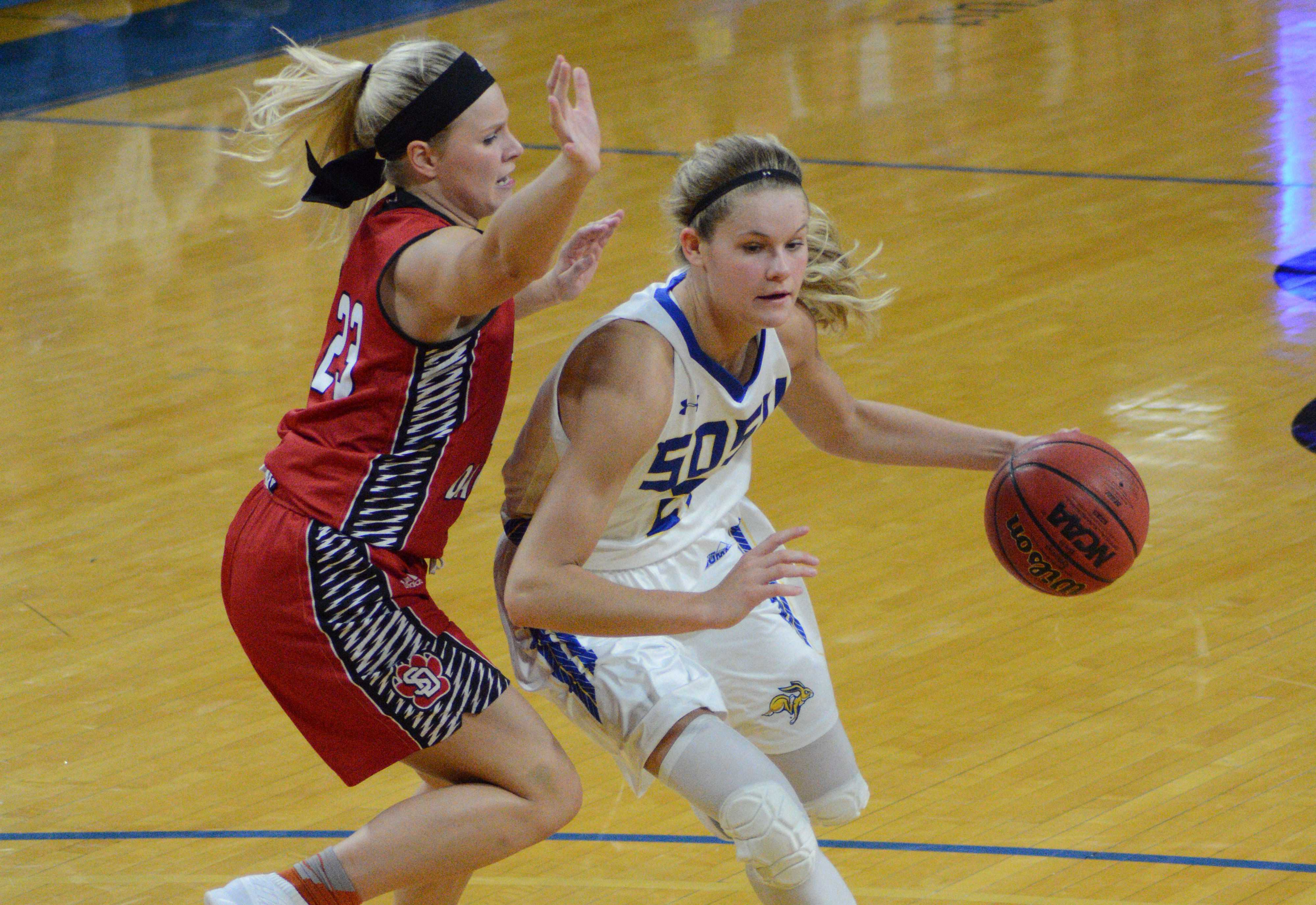 EMILY SEATON Freshman forward Tylee Irwin (21) dribbles around USD sophomore guard Madison McKeever (23). SDSU travels to Fargo, North Dakota Feb. 1 and will face NDSU.
