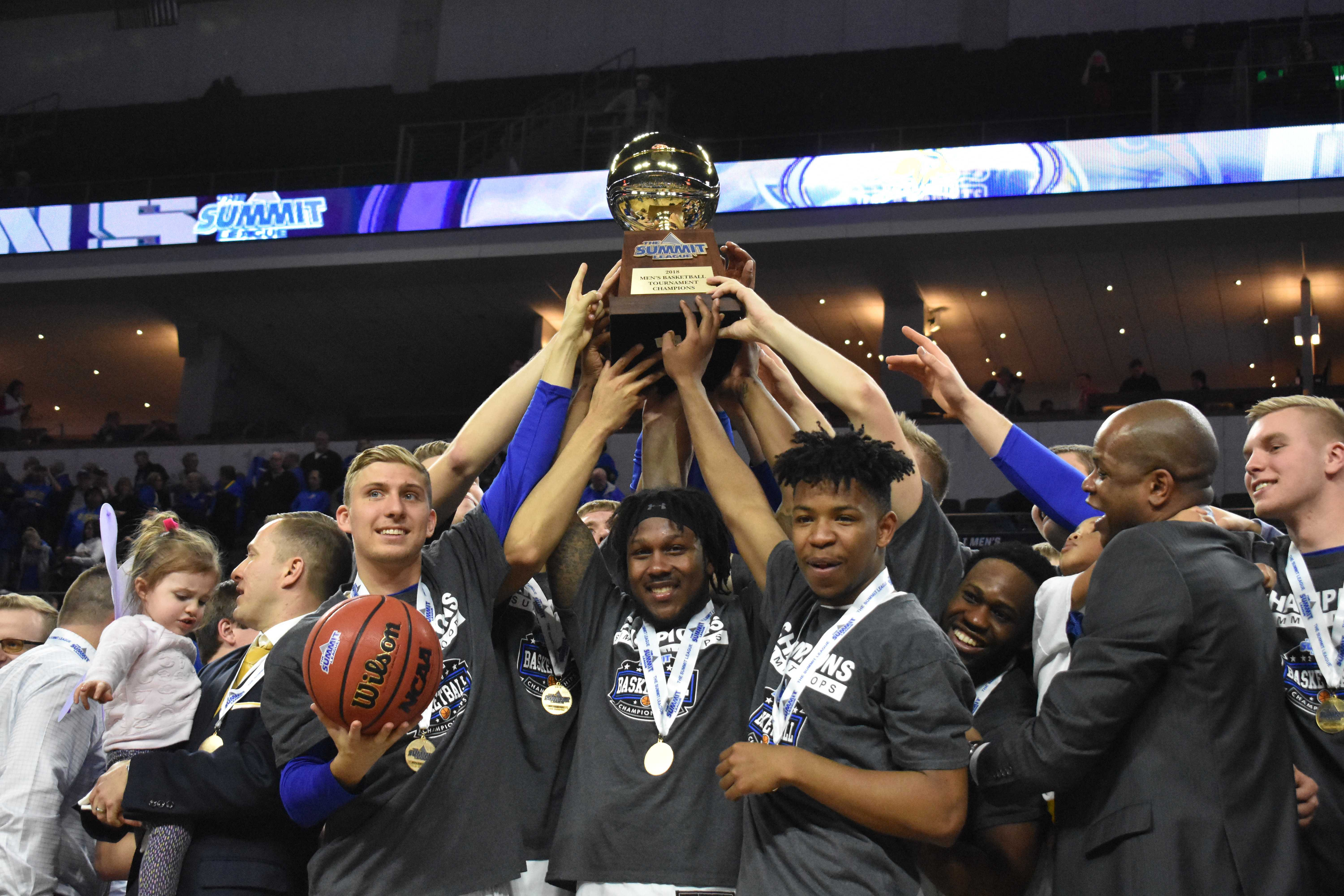 ABBY FULLENKAMP Beau Brown, David Jenkins Jr. and Brandon Key hold the Summit League Championship trophy on March 6. SDSU defeated USD 97-87.