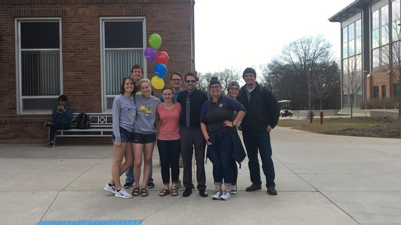 SUBMITTED Ronnie Straub and some of his student-employees gather while admiring the vibrant colors outside Morrill Hall the day he received his glasses.