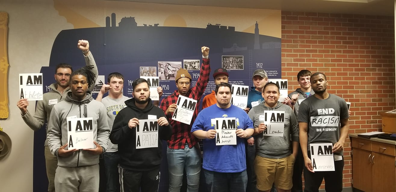 Men who attended the moment of brotherhood pose with signs that describe who they are, like a leader or artist.